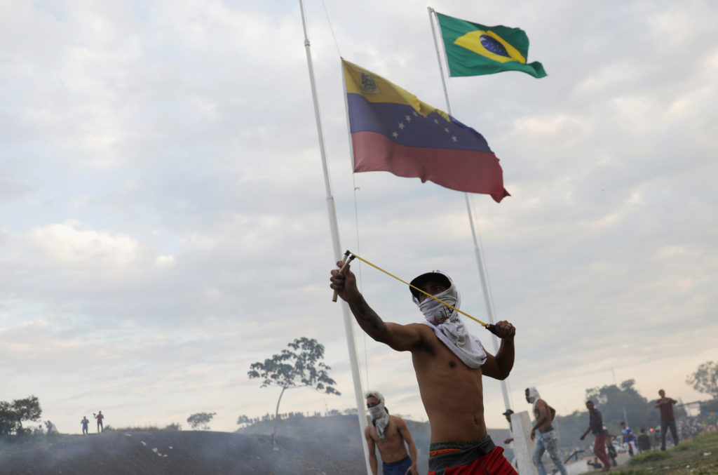 A protester uses a slingshot during clashes with Venezuelan soldiers along the border between Venezuela and Brazil in Pacaraima, Brazil February 23, 2019.  Photo by Ricardo Moraes
