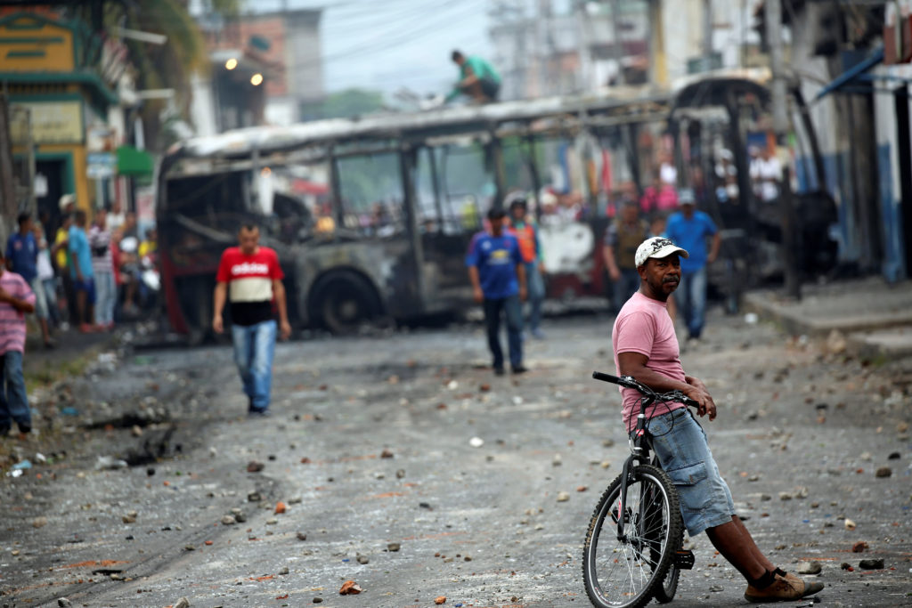 People walk near the remains of a bus burnt during clashes between opposition supporters and Venezuela's security forces, in Urena, Venezuela February 24, 2019. Photo by Andres Martinez Casares/Reuters