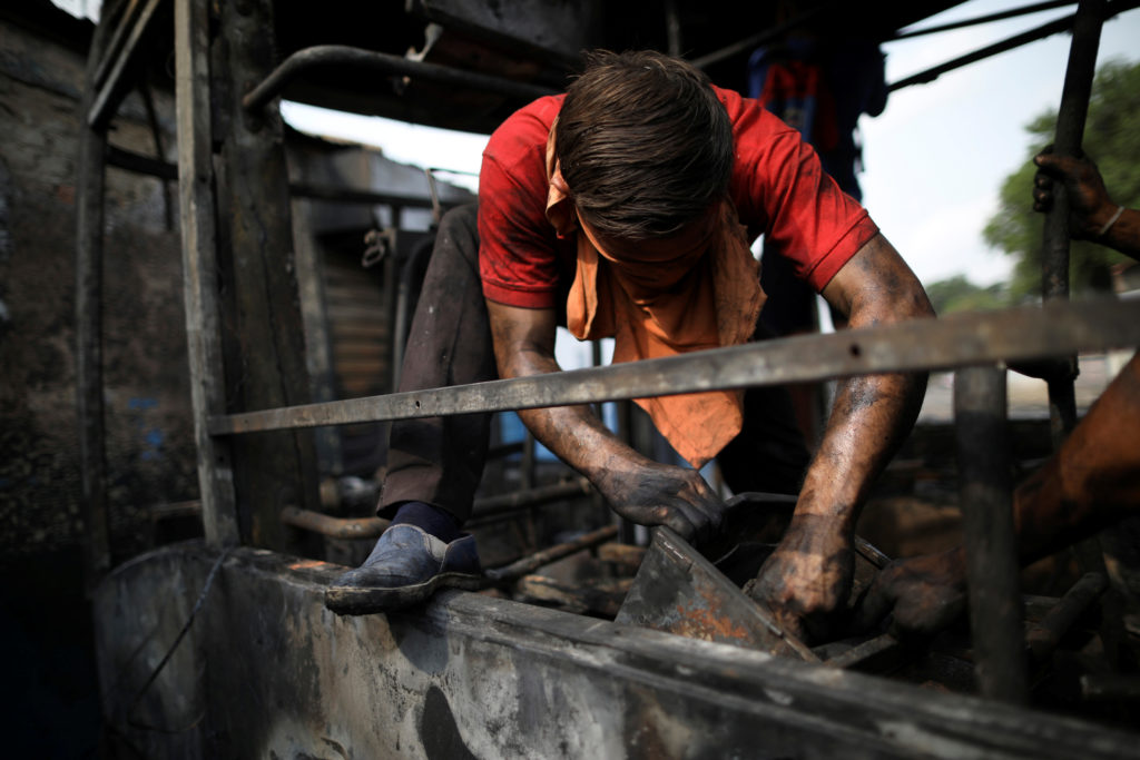 A man dismantles pieces in a bus that was burnt during clashes between opposition supporters and Venezuela's security forces, in Urena, Venezuela February 24, 2019. Photo by Andres Martinez Casares/Reuters