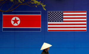 A person walks past a banner showing North Korean and U.S. flags ahead of the North Korea-U.S. summit in Hanoi, Vietnam, on February 25, 2019. Photo by Kim Kyung-Hoon/Reuters
