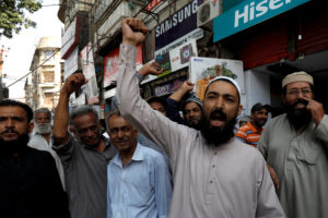 Shopkeepers chant slogans as they celebrate, after Pakistan shot do…