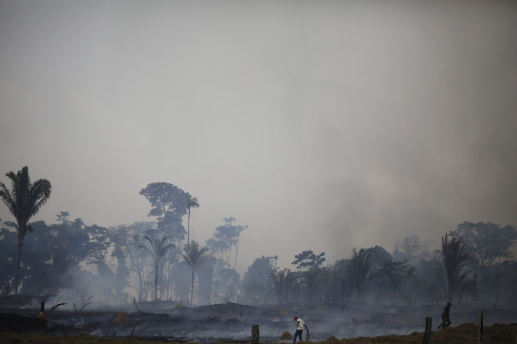 Men try to extinguish a fire at a farm in Rio Pardo next to Bom Futuro National Forest, in the district of Porto Velho, Rondonia State, Brazil, August 30, 2015. The town of Rio Pardo, a settlement of about 4,000 people in the Amazon rainforest, rises where only jungle stood less than a quarter of a century ago. Loggers first cleared the forest followed by ranchers and farmers. Photo by Nacho Doce/Reuters