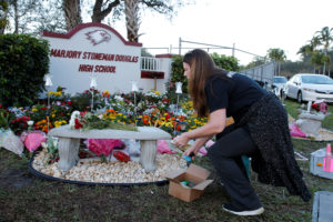 Suzanne Devine Clark places items on a memorial on the one year anniversary of the shooting which claimed 17 lives at Marjory Stoneman Douglas High School in Parkland, Florida. Photo by Joe Skipper/Reuters
