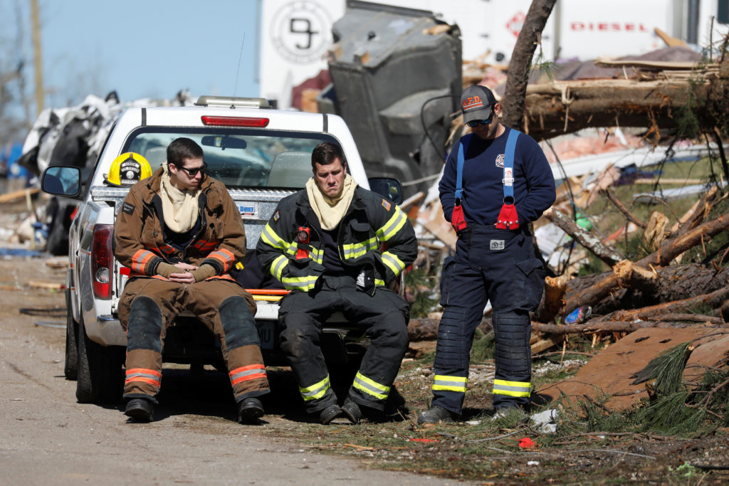 Members of the Auburn fire department are seen outside a devastated…