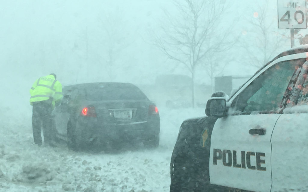 A policeman talks to a driver as snow clogs the roads in Lone Tree, Colorado, U.S. in this March 13, 2019 handout photo. City of Lone Tree, Colo./Handout via REUTERS