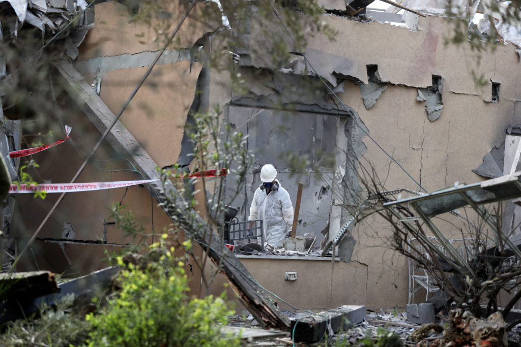 A police sapper inspects a damaged house that was hit by a rocket north of Tel Aviv, Israel. Photo by Ammar Awad/Reuters