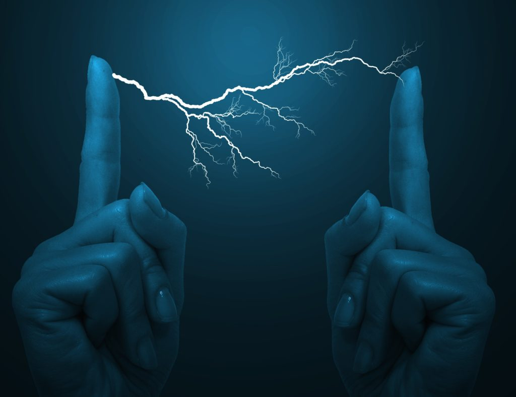 An electrical bolt between a woman's fingers