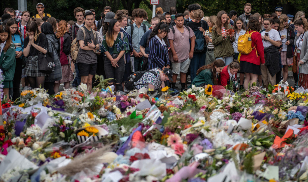Schoolchildren and other well-wishers view flowers and tributes near Al Noor mosque on March 18, 2019 in Christchurch, New...