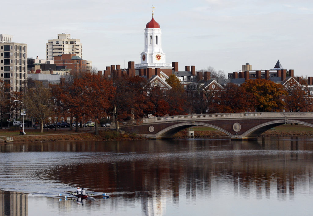 Harvard University is reflected in the Charles River in Cambridge, Massachusetts. A lawsuit claims Harvard profited from photos of slaves. Photo by Jessica Rinaldi/Reuters