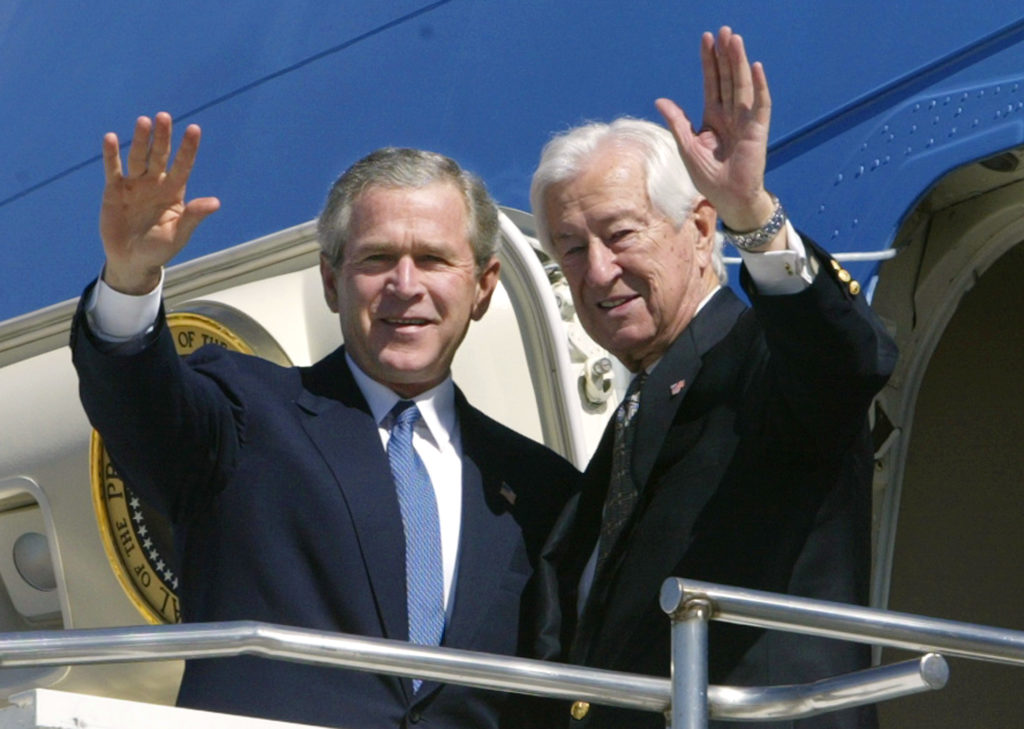U.S. President George W. Bush and Rep. Ralph Hall (R-TX) wave from the steps of Air Force One upon its arrival in Dallas, Texas, March 8, 2004. Hall recently switched parties from Democrat to Republican after nearly a quarter-century as one of the most conservative Democrats in Congress. REUTERS/Kevin Lamarque  KL - RP4DRIBMEWAA
