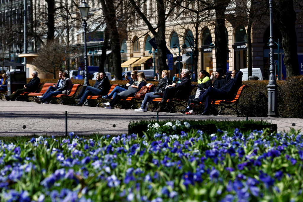 People enjoy a sunnny day at the Esplanade in Helsinki, Finland, which earned the highest ranking in the World Happiness R...