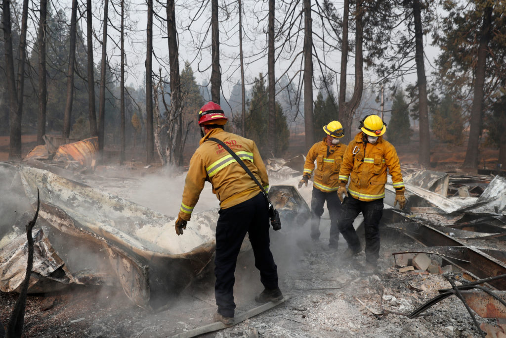Firefighters move debris from a trailer home destroyed by the Camp …