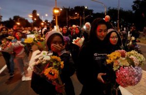 People react as they move the flowers after police removed a police line, outside Masjid Al Noor in Christchurch, New Zealand, March 16, 2019. Photo by Jorge Silva/Reuters