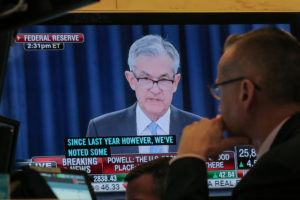 A trader watches U.S. Federal Reserve Chairman Jerome Powell on a screen during a news conference following the two-day Federal Open Market Committee policy meeting, on the floor at the New York Stock Exchange on March 20, 2019. Stock investors are one of the main beneficiaries of the Fed's decision to hold raise interest rates steady. Photo by Brendan McDermid/Reuters