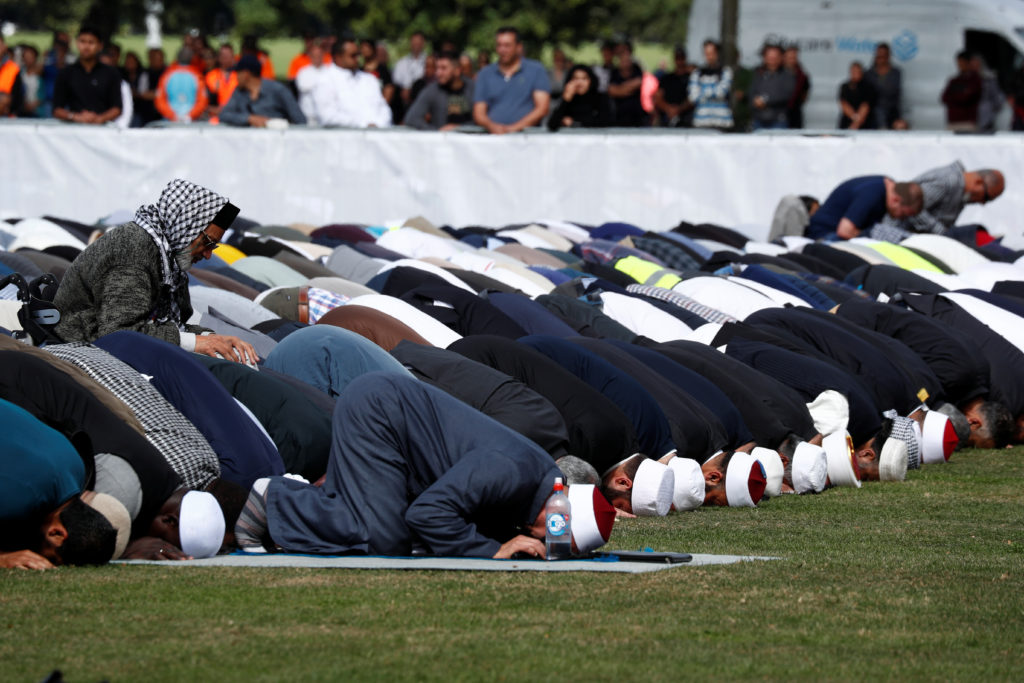 People perform the Friday prayers at Hagley Park outside Al-Noor mosque in Christchurch, New Zealand on March 22, 2019, one week after an attack on two mosques killed dozens of worshippers. Photo by Edgar Su/Reuters