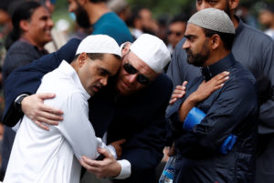 People comfort each other before the Friday prayers at Hagley Park outside Al-Noor mosque in Christchurch, New Zealand March 22, 2019. Photo by Edgar Su/Reuters