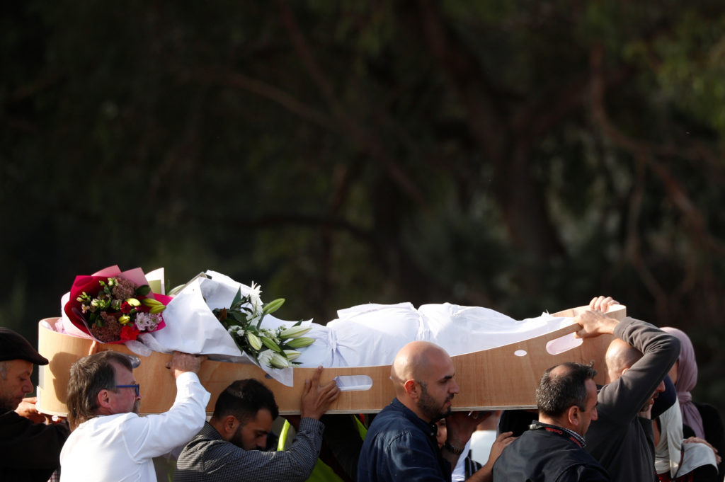People carry the body of a victim during a burial ceremony for victims of the mosque attacks, at the Memorial Park Cemetery in Christchurch, New Zealand on March 22, 2019. Photo by Edgar Su/Reuters
