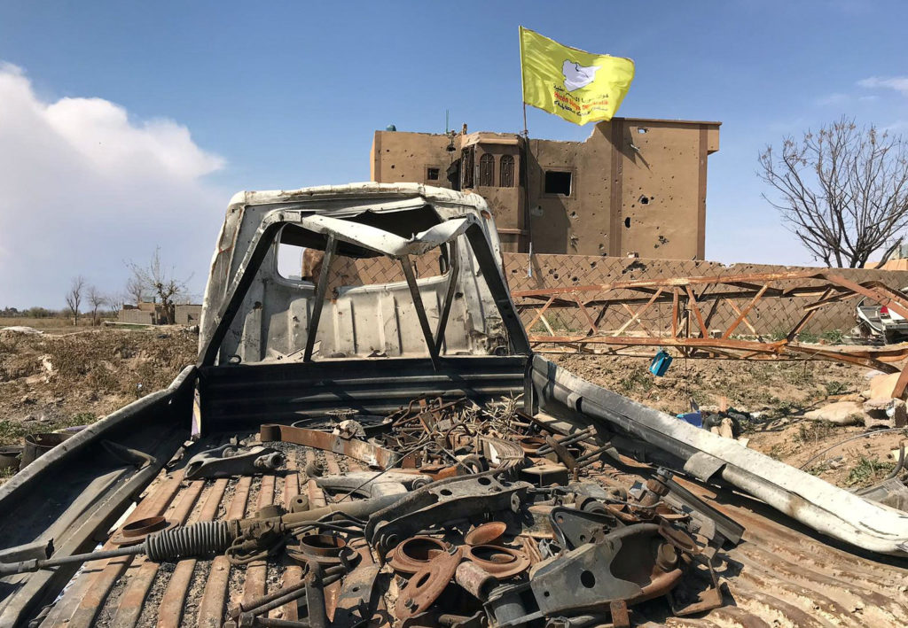 A Syrian Democratic Forces flag flutters on a damaged building in the village of Baghouz, Deir Al Zor province, Syria, March 23, 2019. Photo by Stringer/Reuters