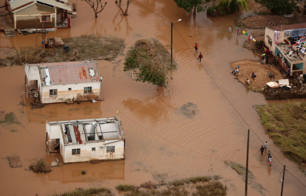 People walk through floodwater near Beira, Mozambique, in the aftermath of Cyclone Idai, March 23, 2019. Photo by Mike Hutchings/Reuters