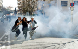 "Protesters run away as tear gas is fired during 19th round of ""yellow vests"" protests in Nice, France, March 23, 2019. Photo by Eric Gaillard"