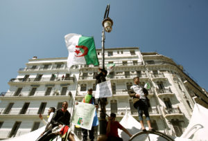 A demonstrator holds a national flag while standing on a street pole during a protest to demand the removal of President Abdelaziz Bouteflika in Algiers, Algeria on March 29, 2019. Photo by Ramzi Boudina/Reuters