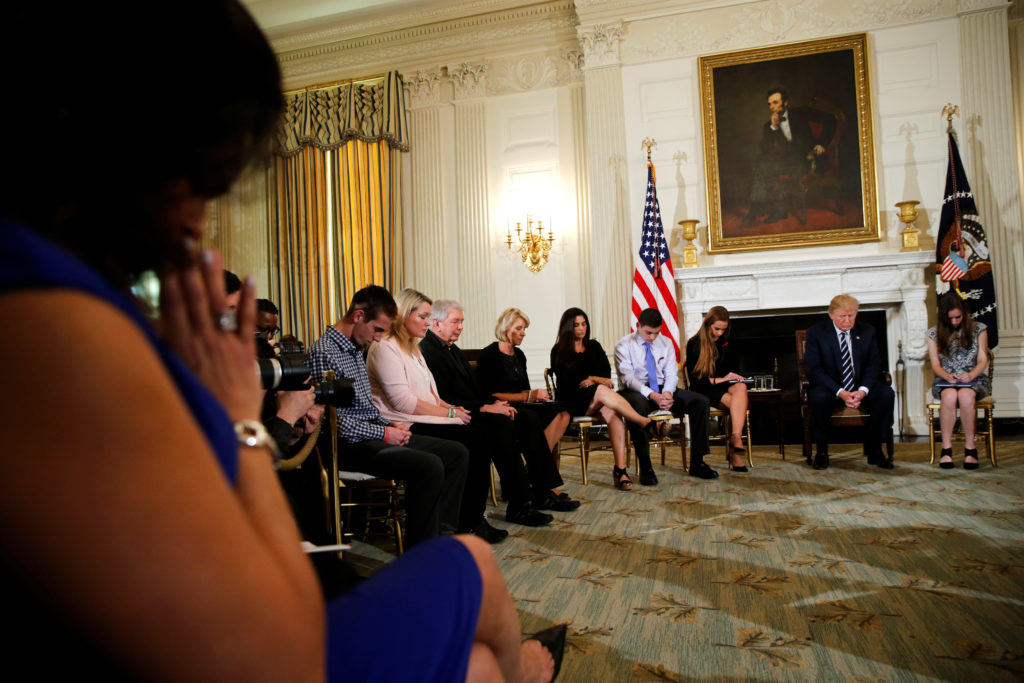 President Donald Trump bows his head in prayer with participants at a listening session with Marjory Stoneman Douglas High School shooting survivors and students at the White House in Washington on February 21, 2018. Photo by Jonathan Ernst/Reuters
