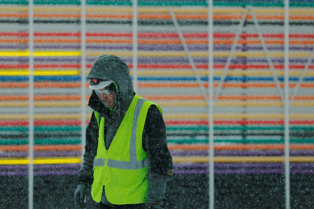 A construction worker walks through a winter snow storm in Boston, …