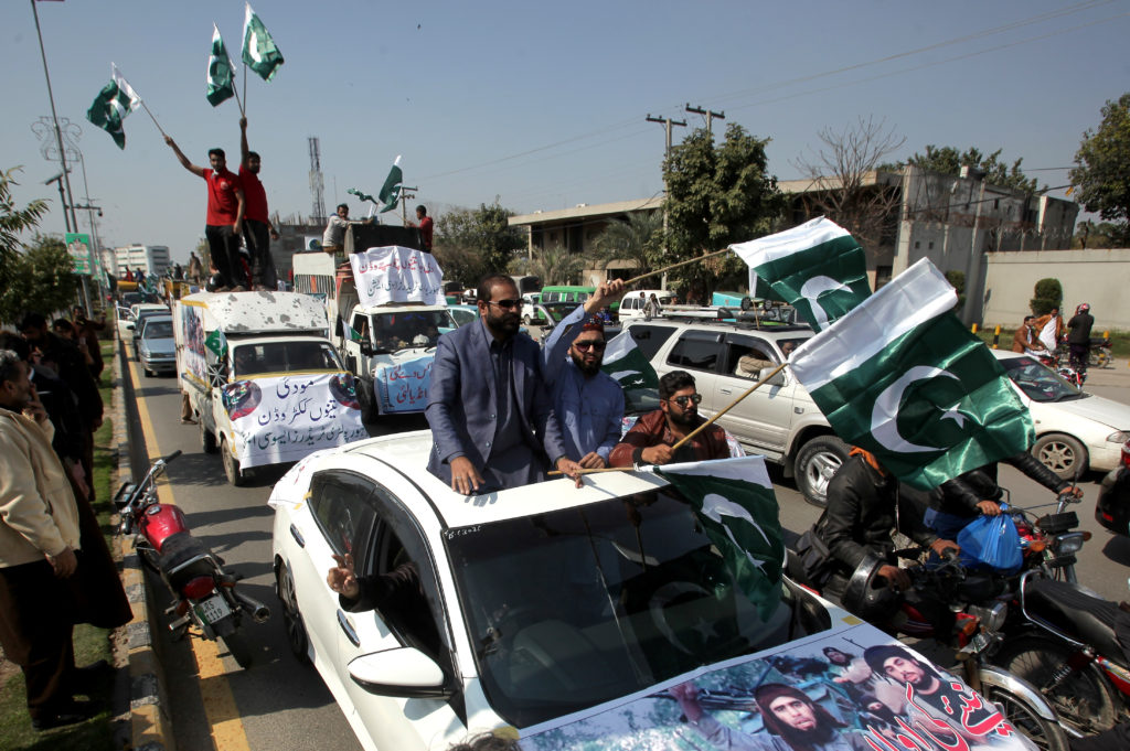 People carry national flags as they celebrate after Pakistan shot down two Indian military aircrafts in Lahore Pakistan