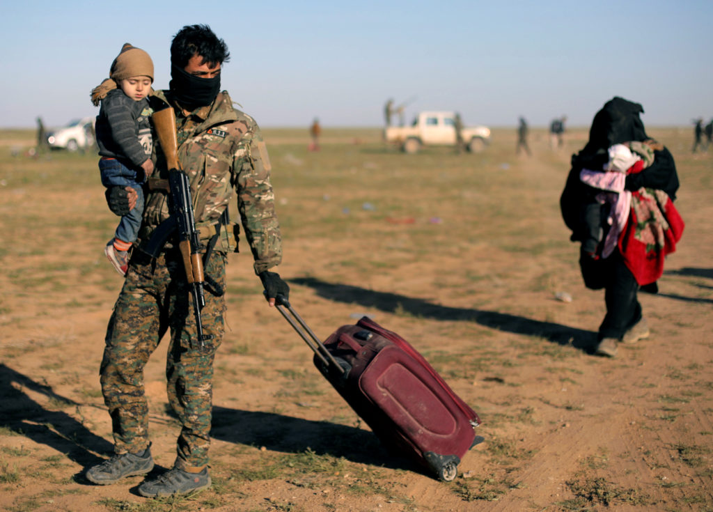 A fighter from Syrian Democratic Forces (SDF) holds a baby near the village of Baghouz, Deir Al Zor province, Syria March 1, 2019. Photo by Rodi Said/Reuter