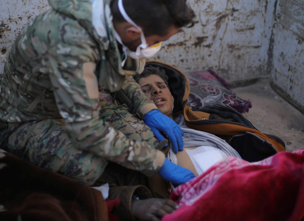 A member of the Syrian Democratic Forces (SDF) delivers care to Hareth Najem, an Iraqi orphan, near the village of Baghouz...