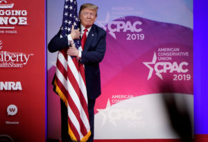U.S. President Donald Trump hugs the U.S. flag as he arrives to speak at the Conservative Political Action Conference (CPAC) annual meeting at National Harbor in Oxon Hill, Maryland, U.S., March 2, 2019. Photo by Joshua Roberts/Reuters