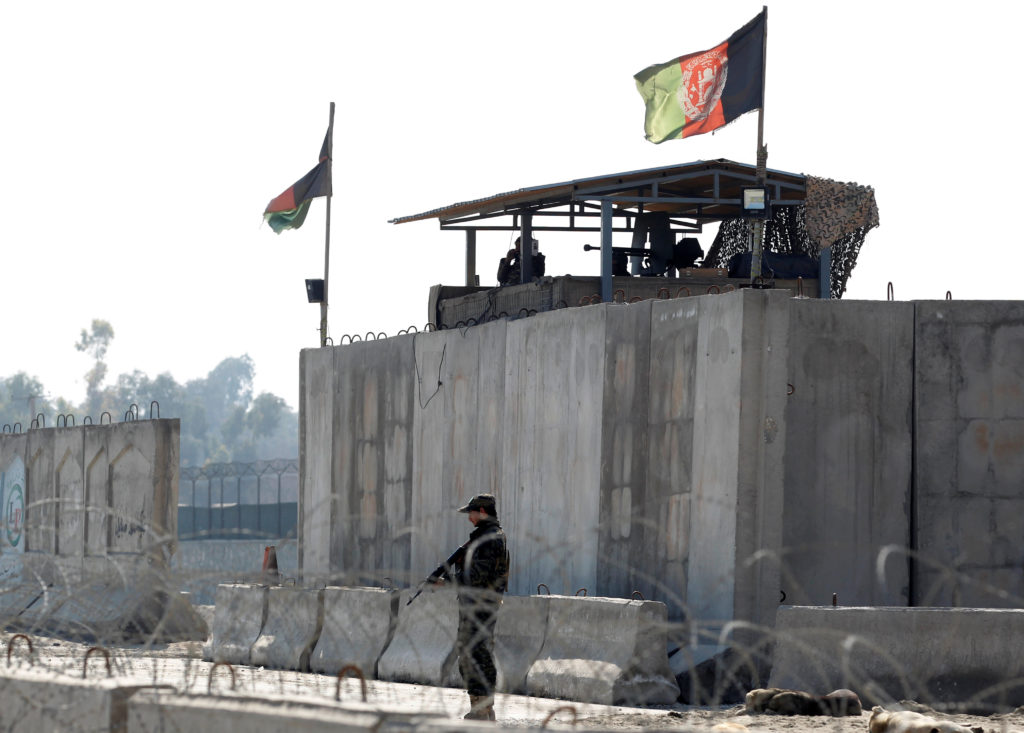 Afghan security forces stand guard near the site of an attack in Ja…