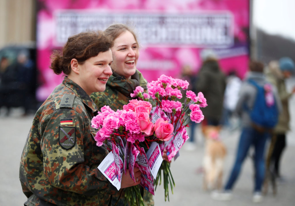 Female soldiers of the German Armed Forces (Bundeswehr) distribute flowers to women during the International Women's Day near the Brandenburg Gate in Berlin, Germany. Photo by Hannibal Hanschke/Reuters
