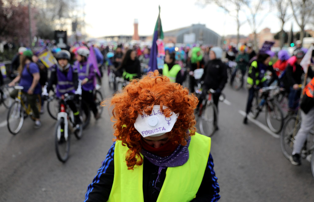 "A woman wears a mask that reads ""Feminist Strike"" as she takes part in a bike protest during a nationwide feminist strike on International Women's Day in Madrid, Spain. Photo by Sergio Perez/Reuters"