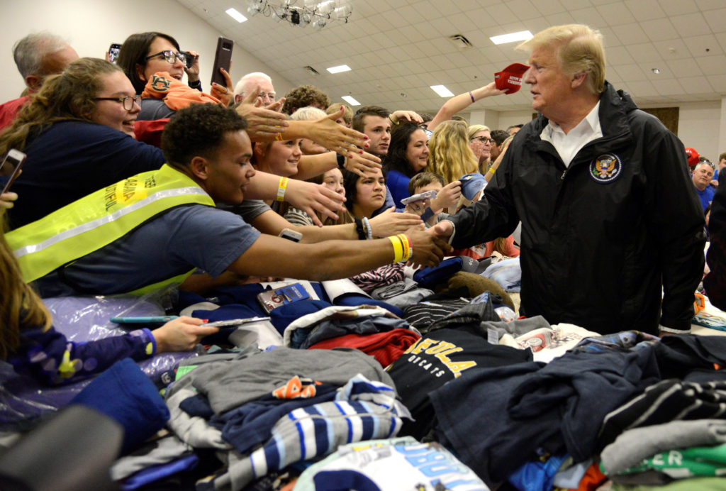 U.S. President Donald Trump greets volunteers who have sorted donated clothing at the Providence Baptist Church in Beauregard, Alabama.           Photo by Mike Theiler/Reuters