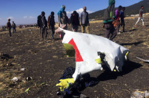 People walk past a part of the wreckage at the scene of the Ethiopian Airlines Flight ET 302 plane crash, near the town of Bishoftu, southeast of Addis Ababa, Ethiopia March 10, 2019. Photo by Tiksa Negeri/Reuters