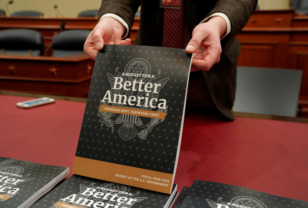 An aide holds up a copy of Volume 1 of U.S. President Donald Trump's budget for Fiscal Year 2020 after it was delivered by the Office of Management and Budget (OMB) to the House Budget Committee room on Capitol Hill in Washington U.S., March 11, 2019. REUTERS/Kevin Lamarque - RC1E9ABFB580