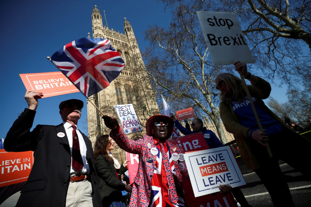 Pro-Brexit and anti-Brexit protesters stand outside of the Houses o…