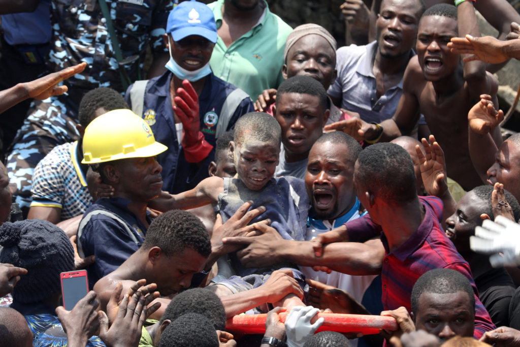 Men carry a boy who was rescued at the site of a collapsed building…