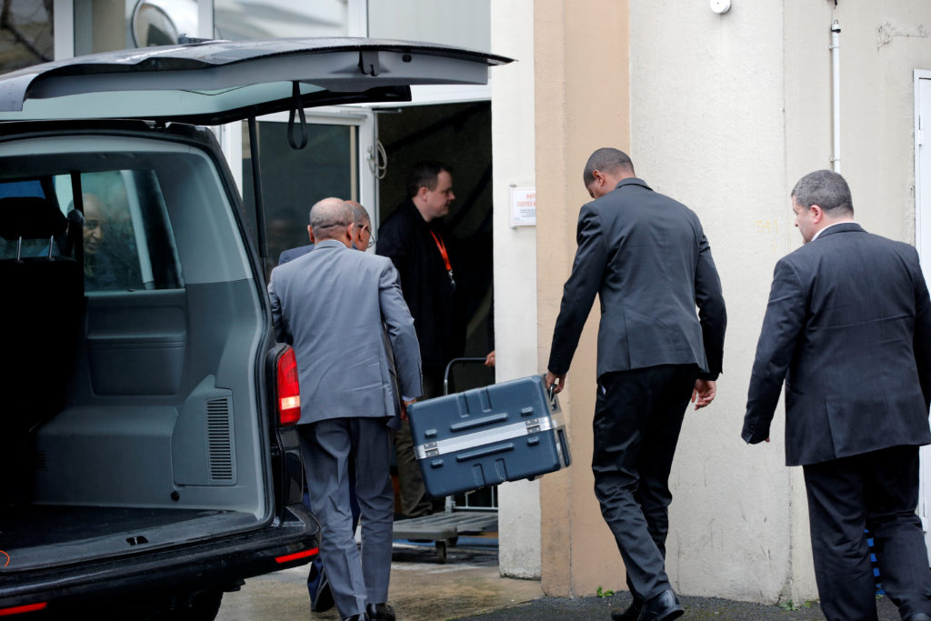 Men unload a case from a diplomatic car from the Ethiopian Embassy outside the headquarters of France's BEA air accident i...