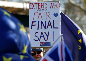 An anti-Brexit protester holds a placard outside the Houses of Parliament in London as members of Parliament voted to delay the deadline for when the UK would leave the EU. Photo by Peter Nicholls/Reuters