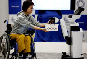 Toyota's Human Support Robot delivers a basket to a woman in a wheelchair at a demonstration of Tokyo 2020 Robot Project for Tokyo 2020 Olympic Games. Photo b y Kim Kyung-hoon/Reuters