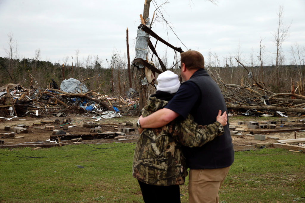 A man hugs Julie Morrison while looking at the remains of her home following a string of tornadoes that resulted in several fatalities in Beauregard, Alabama, U.S., March 4, 2019. Photo by REUTERS/Elijah Nouvelage