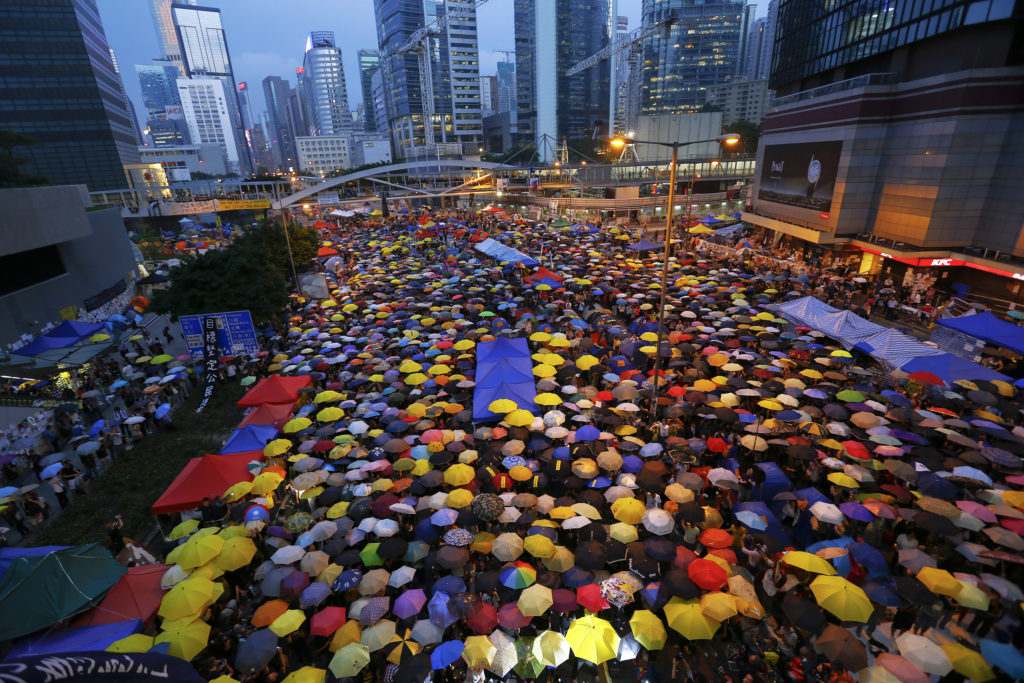 """FILE PHOTO: Protesters open their umbrellas, symbols of pro-democracy movement, as they mark exactly one month since they took the streets in Hong Kong's financial central district on October 28, 2014. The protests became known as the """"Umbrella Movement."""" Photo by Damir Sagolj/Reuters"""