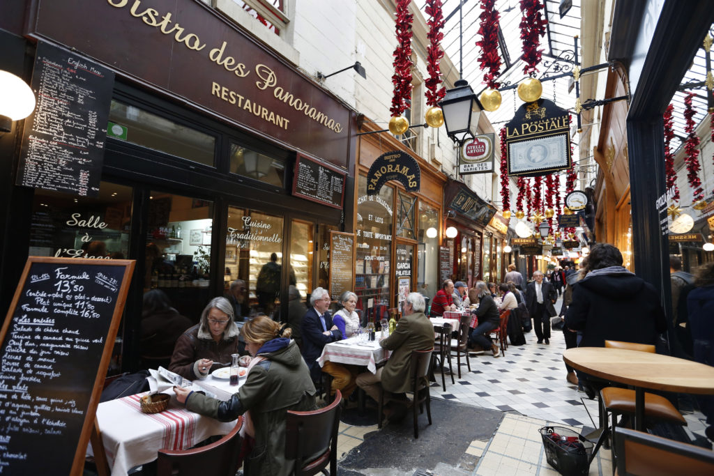 People sit at tables as they have lunch outside bistros in a covered passageway, the Passage des Panoramas, in Paris, Fran...