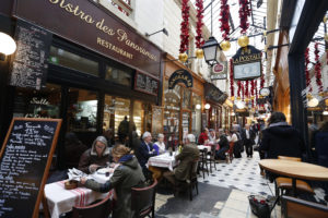 People sit at tables as they have lunch outside bistros in a covered passageway, the Passage des Panoramas, in Paris, France. Photo by Charles Platiau/Reuters
