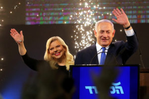 Israeli Prime Minister Benjamin Netanyahu and his wife Sara wave as Netanyahu speaks following the announcement of exit polls in Israel's parliamentary election at the party headquarters in Tel Avi on April 10, 2019. Photo by REUTERS/Ammar Awad