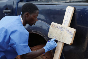 A Congolese red cross worker writes on a cross the name of Congolese woman Kahambu Tulirwaho who died of Ebola, before a burial service at a cemetery in Butembo in the Democratic Republic of Congo, March 28, 2019. Photo by Baz Ratner/Reuters
