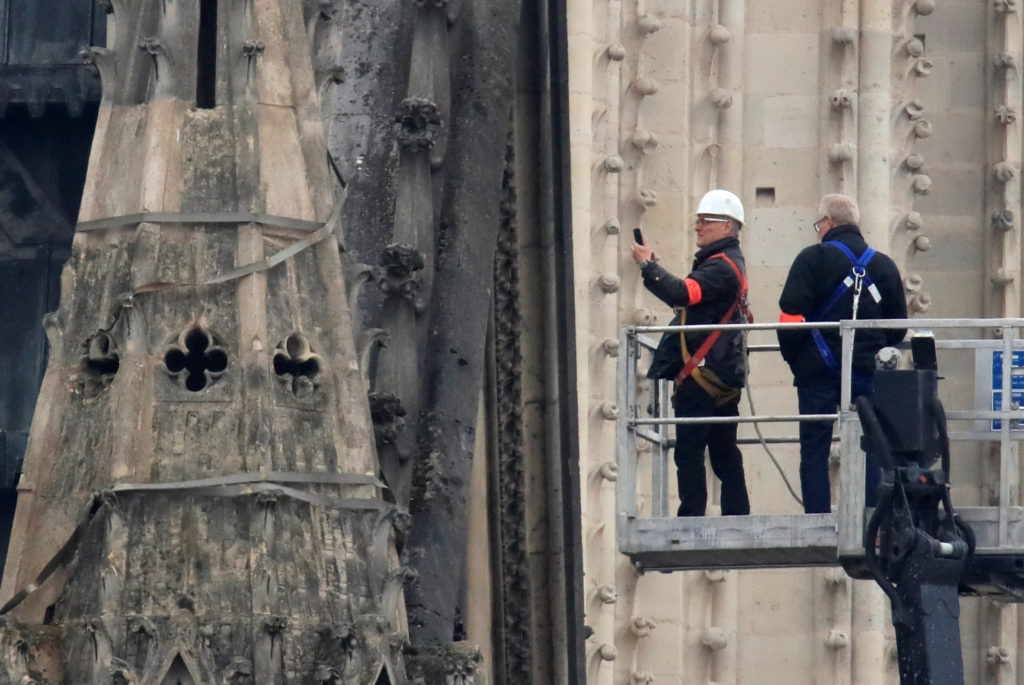 Officials work at Notre-Dame Cathedral after a massive fire devastated large parts of the gothic gem in Paris. Photo by Gonzalo Fuentes/Reuters