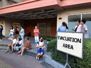 Residents sit outside after being evacuated from the condominium building after an earthquake in Makati City, Philippines on April 22, 2019. Photo by Neil Jerome Morales/Reuters